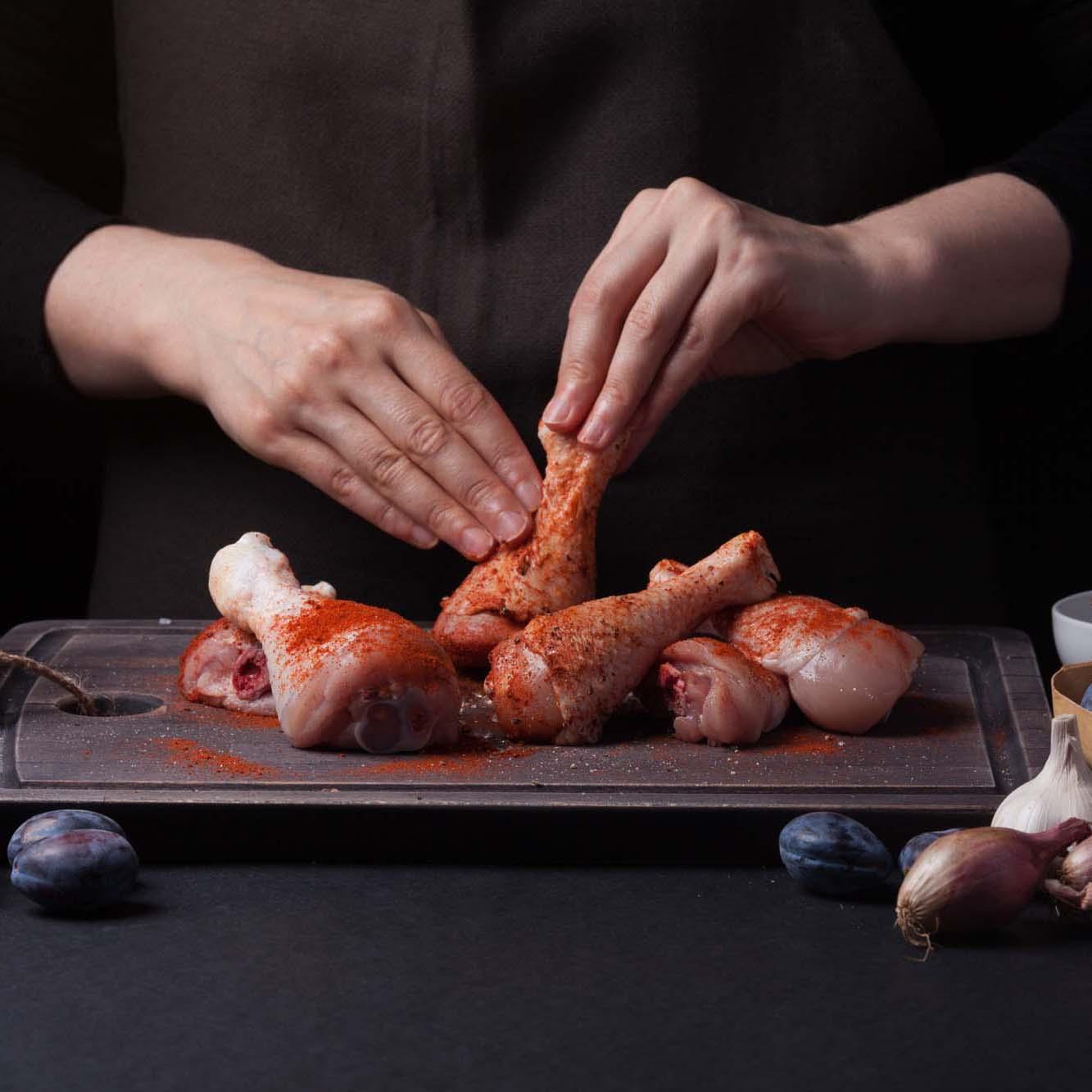 Woman,Chef,Rubs,Salt,With,Fresh,Raw,Chicken,Drumsticks,On