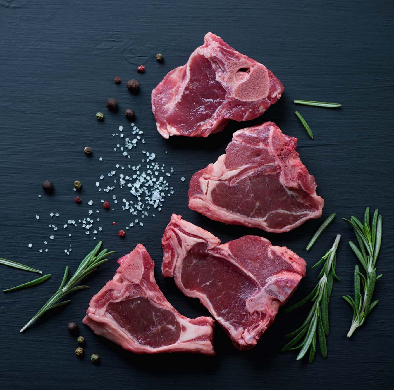 Raw,T-bone,Lamb,Steaks,With,Seasonings,On,A,Black,Wooden